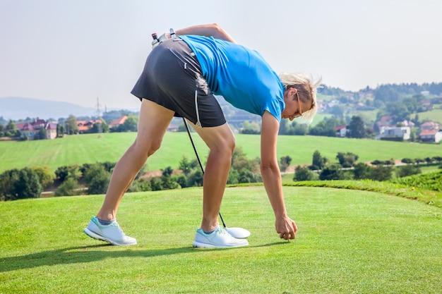 Golfista profesional femenino conduciendo un tee en el green en el campo de golf de zlati gric en eslovenia