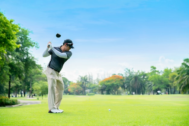 Golfista que golpea el tiro de golf con el club en curso durante las vacaciones de verano.