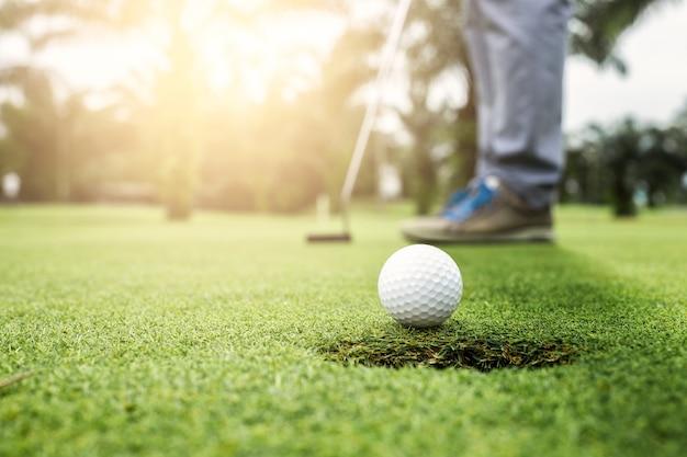 El golfista que pone la bola de golf se acerca al hoyo del golf en el golf verde