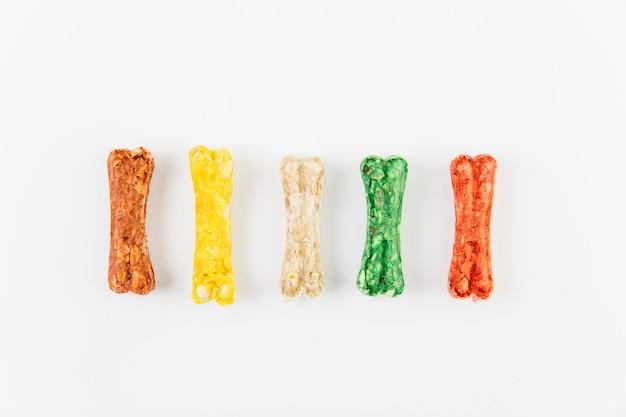 Golosinas de colores para perro sobre superficie blanca.