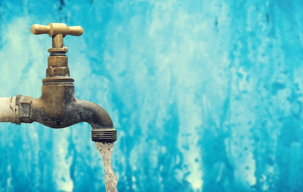 Golpecito del vintage, grifo de la fuente de agua que se escapa, tubo de cobre amarillo con el fondo azul.