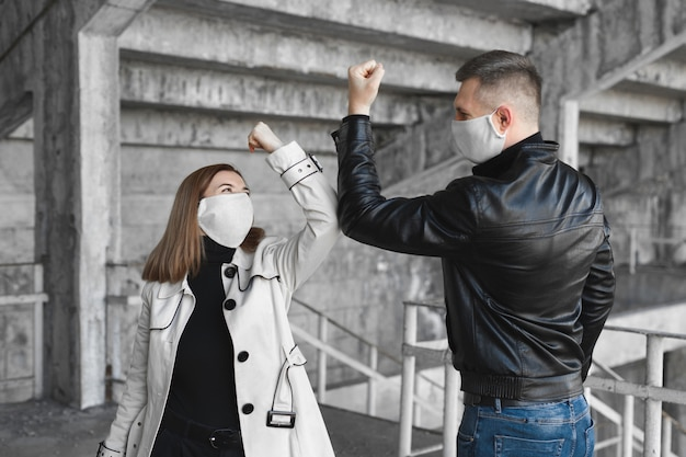 Golpes en el codo. una nueva forma de saludo para evitar la propagación del coronavirus, covid19. un hombre y una mujer se golpean los codos en lugar de abrazarse o apretarse las manos