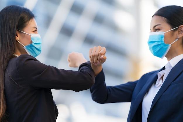 Golpes en los codos, nuevo normal, colegas femeninas con máscaras protectoras que saludan los codos golpeados