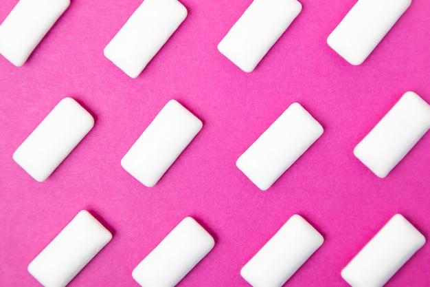 Goma de mascar, gragea blanca sobre un rosado brillante.
