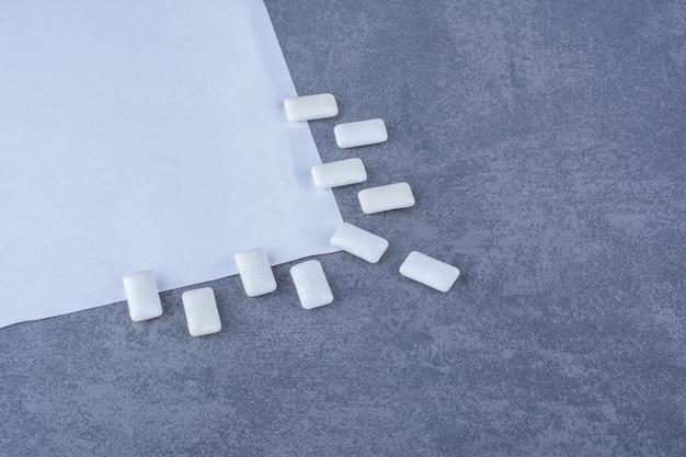 Gomas de mascar alineadas decorativamente en el borde de una hoja de papel sobre una superficie de mármol