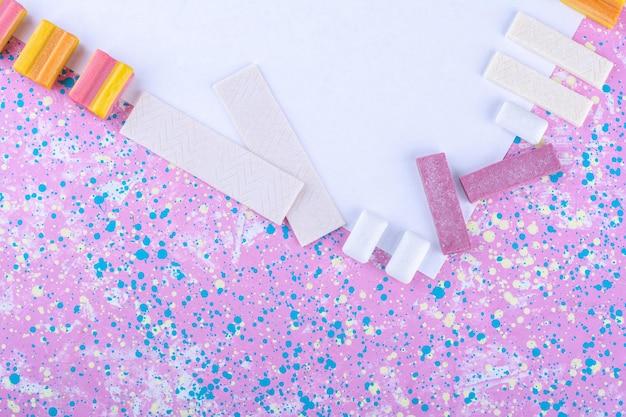 Gomas de mascar bordeando una pizarra blanca sobre una superficie colorida