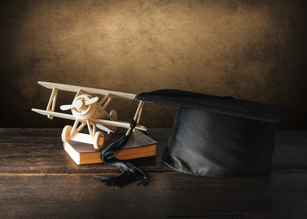 Gorra de graduación, sombrero con avión de juguete de madera en mesa de madera