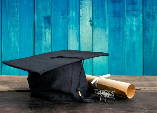 Gorra de graduación, sombrero con papel de grado en la mesa de madera, fondo de madera vintage vacío listo