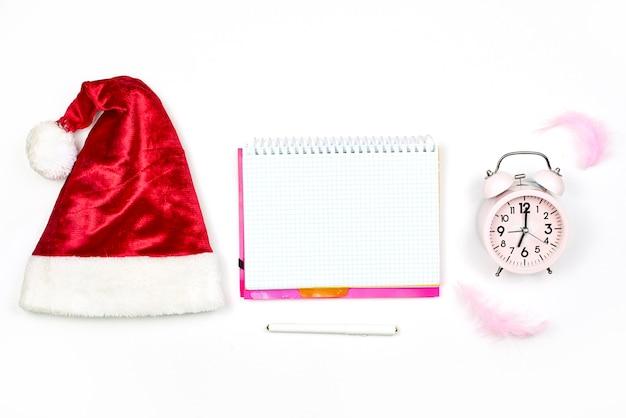 Gorra de santa, bloc de notas vacío y despertador en blanco. bloc de notas con navidad