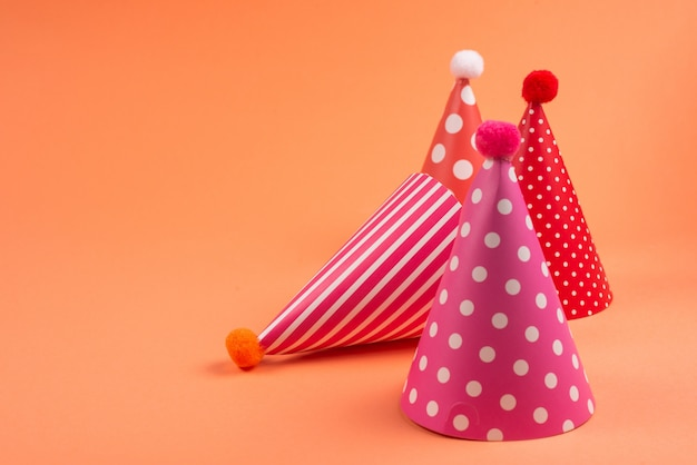 Gorras de cumpleaños coloridas en naranja