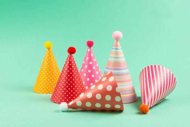 Gorras de cumpleaños colorido sobre fondo de menta.