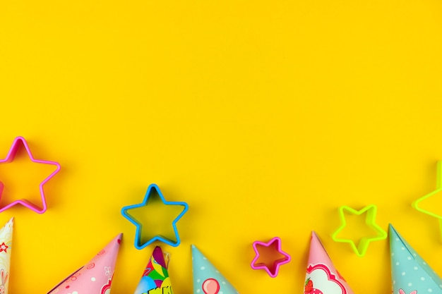 Gorras de fiesta de cumpleaños, globos y estrellas sobre fondo amarillo con copyspace