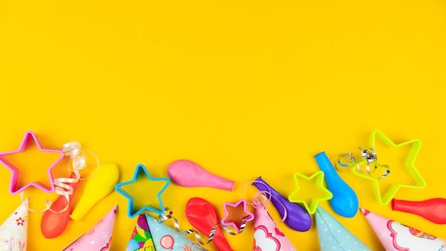Gorras de fiesta de cumpleaños, globos y estrellas sobre fondo amarillo