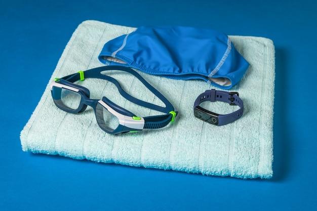Gorro de baño, gafas y pulsera inteligente sobre una toalla sobre una superficie azul. accesorios para nadar en la piscina.