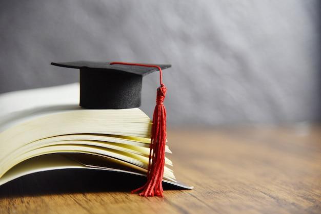 Gorro de graduación en un libro sobre la mesa de madera