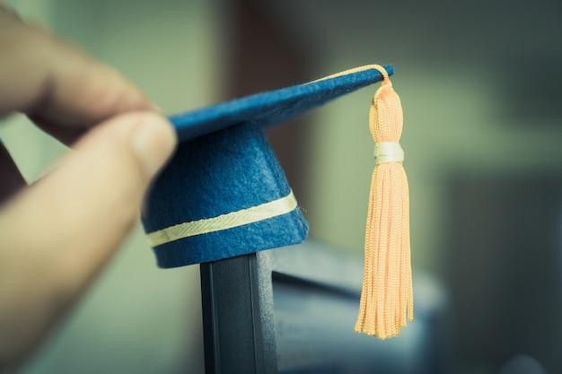 Gorro de graduación en manos muestra éxito en educación, aprendizaje, estudios internacionales en el extranjero.