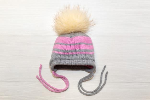 Gorro infantil de lana tejida con pompón, sobre un fondo blanco.