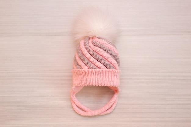 Gorro de lana tejida infantil rosa con pompón, sobre un fondo blanco.
