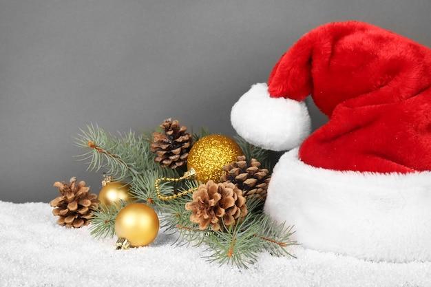 Gorro de papá noel con decoración navideña en superficie gris