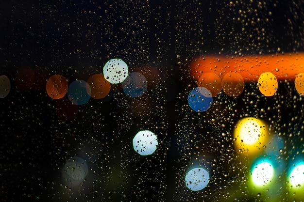 Gota de agua en la ventana y luces bokeh