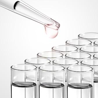 Gota de líquido de la pipeta de vidrio de laboratorio al tubo de ensayo.