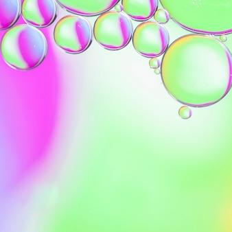Gotas de aceite degradado en el agua en el fondo colorido