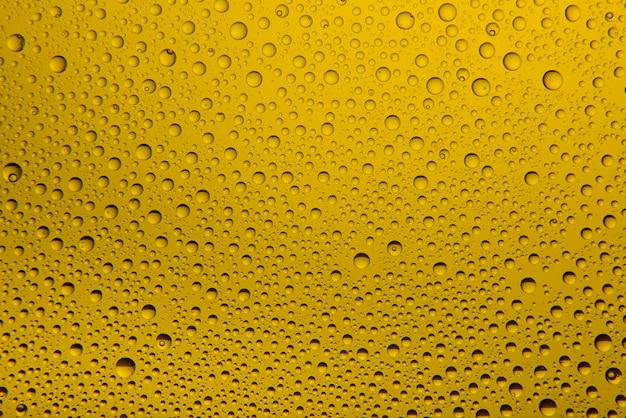 Gotas de agua amarilla sobre vidrio
