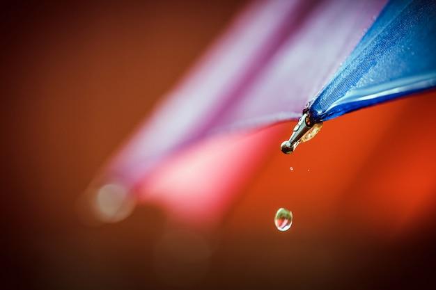 Gotas de agua caen del paraguas.