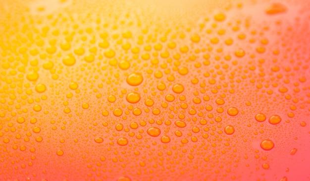 Gotas de agua de cerca en una superficie amarilla