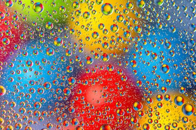 Gotas de agua coloreadas sobre vidrio.