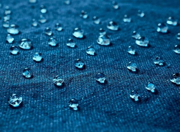 Gotas de agua de lluvia sobre tela impermeable azul.