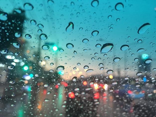 Gotas de agua en el parabrisas, tráfico en la ciudad en un día lluvioso, bokeh colorido.