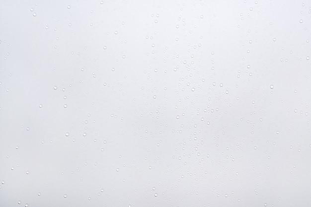 Gotas de agua sobre fondo de superficie blanca.