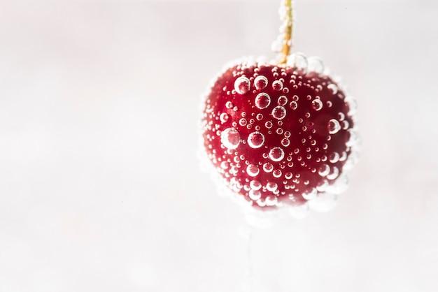 Gotas de agua sobre jugosa cereza roja