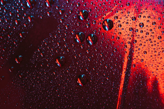 Gotas de agua sobre el vidrio reflectante rojo