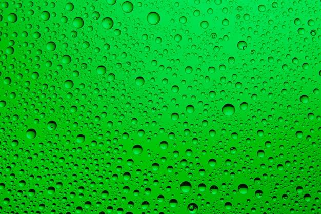Gotas de agua verde sobre vidrio
