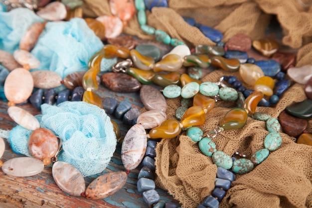 Gotas y collares multicolores de piedras semipreciosas en un viejo fondo de madera. joyas de mujer
