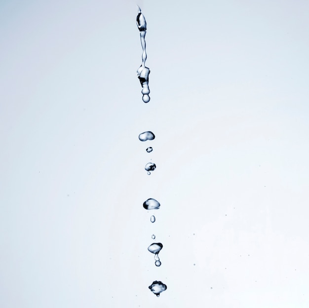 Gotas de líquido transparente sobre fondo blanco con espacio de copia