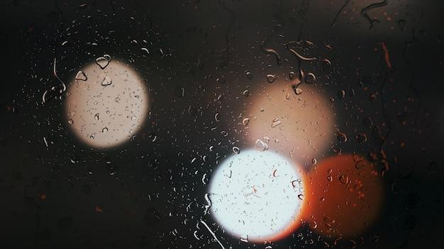 Gotas de lluvia caen por el cristal contra el fondo bokeh de coches en movimiento