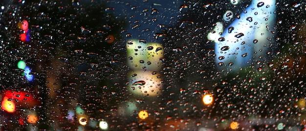 Gotas de lluvia en el parabrisas del automóvil durante la conducción en la calle urbana por la noche