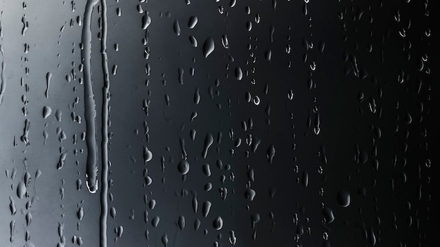 Gotas de lluvia sobre fondo negro de vidrio