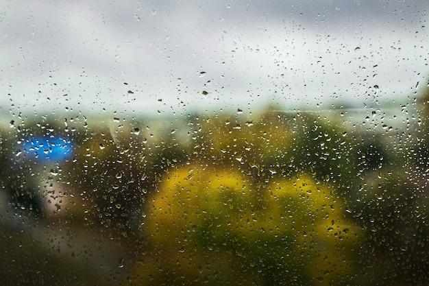 Gotas de lluvia en la ventana de la gran ciudad. árboles en el fondo
