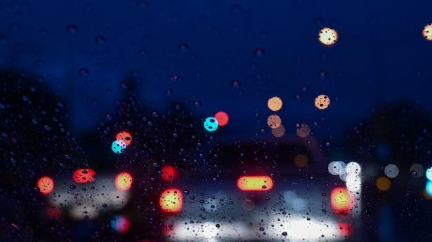 Gotas de lluvia en la ventana con luz de carretera bokeh en la noche lluviosa.