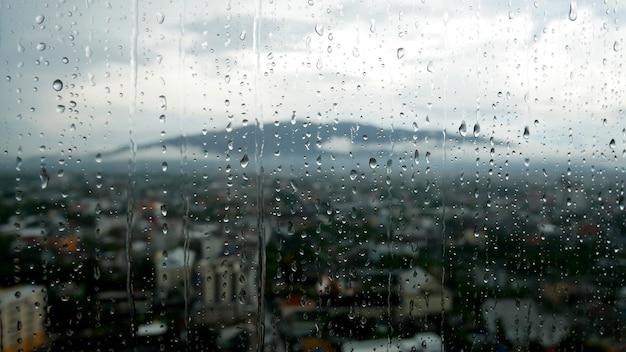 Gotas de lluvia en la ventana y la montaña con la ciudad en el fondo borroso.