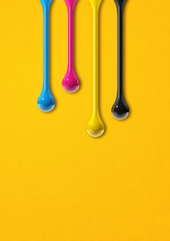 Gotas de tinta cmyk 3d aisladas sobre fondo de papel amarillo. ilustración