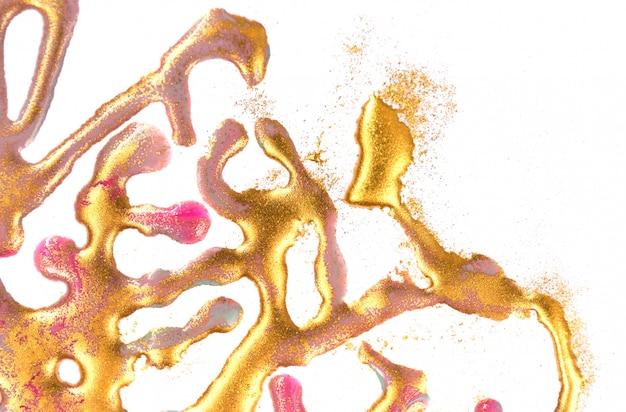 Gotas de tinta dorada, manchas y lentejuelas sobre fondo de papel blanco