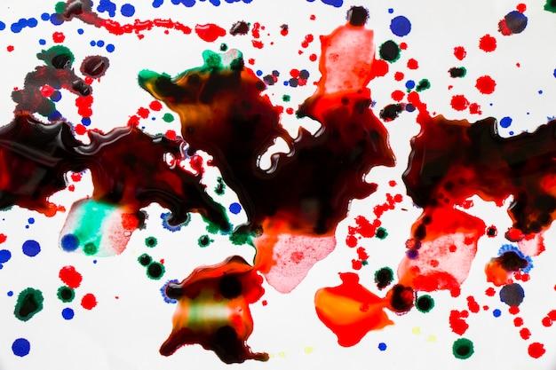 Gotas de tinta sobre el papel, salpicaduras de tinta roja, verde y azul, pintura y dibujo