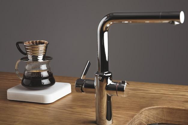 Gotee la cafetera japonesa sobre pesas blancas simples detrás del grifo plateado en la cafetería sobre una mesa de madera gruesa.
