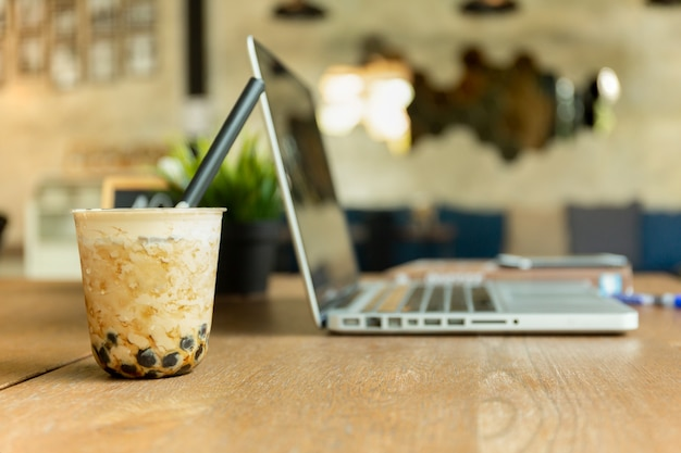 Gotee el té helado leche con el ordenador portátil en la tabla de madera en café.