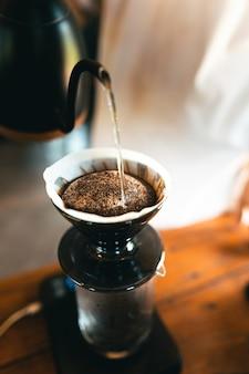 Goteo de café, barista vertiendo agua sobre el café molido con filtro, preparando café